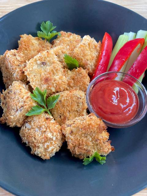 Vegan tofu nuggets served with ketchup.