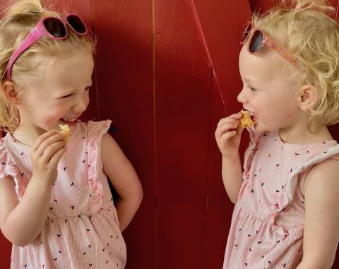 Twins are eating delicious vegan tofu nuggetes.